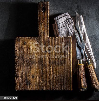 Cooking background. Vintage cutting board and cutlery. Slate background