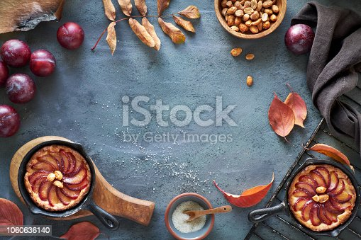 istock Cooking background with red plums, plum crumble cakes, towel, caramelized peanuts, autumn leaves, copy-space 1060636140