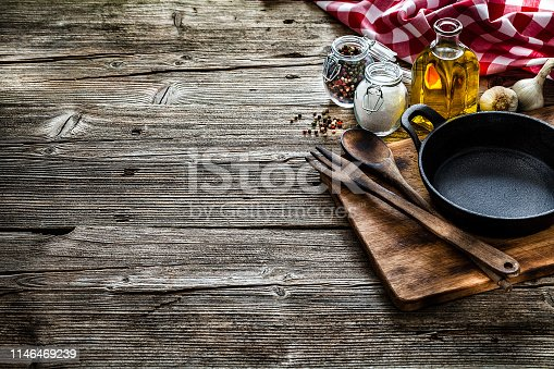 Cooking backgrounds: Top view of a black cast iron pan, salt, olive oil, peppercorns arranged at the right of a rustic wooden kitchen table leaving a useful copy space for text and/or logo at the center left. A gingham tablecloth is at the top right corner of the table. Predominant colors are brown and red. Low key DSRL indoors photo taken with Canon EOS 5D Mk II and Canon EF 24-105mm f/4L IS USM Wide Angle Zoom Lens