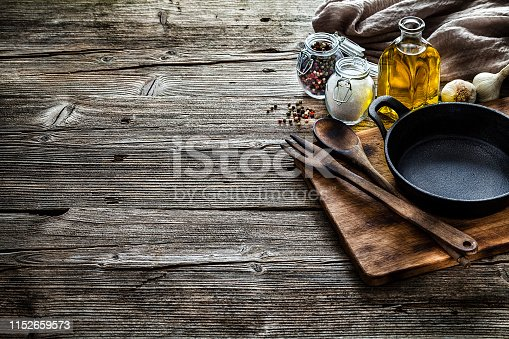 Cooking backgrounds: Top view of a black cast iron pan, salt, olive oil, peppercorns arranged at the right of a rustic wooden kitchen table leaving a useful copy space for text and/or logo at the center left. A brown tablecloth is at the top right corner of the table. Predominant color is brown. Low key DSRL indoors photo taken with Canon EOS 5D Mk II and Canon EF 24-105mm f/4L IS USM Wide Angle Zoom Lens