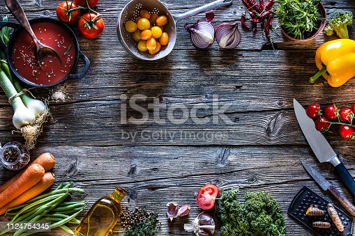 Cooking concepts: top view of a rustic wooden table with fresh organic vegetables and kitchen utensils placed all around the border making a frame and leaving useful copy space for text and/or logo at the center. Vegetables included in the composition are tomatoes, onion, rosemary, broccoli, bell pepper, lettuce, garlic, green beans, carrots, and others. Some kitchen utensils like a cast iron pan, colander, kitchen knives, grater, olive oil bottle, and a glass container filled with dried spices complete the composition. DSRL studio photo taken with Canon EOS 5D Mk II and Canon EF 70-200mm f/2.8L IS II USM Telephoto Zoom Lens