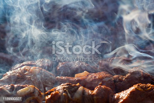 Cooking barbecue on the grill with smoke. Meat on grill. Morning BBQ. Cook fresh marinated meat with onions. Grill marinated barbecue is prepared on the grill on the coals.
