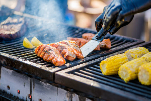 Cooking BBQ Fish.Gloved hands turn pieces of fish on the grill. stock photo
