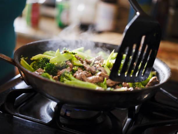 koken rundvlees en broccoli roerbak in hete pijn in huis keuken foto