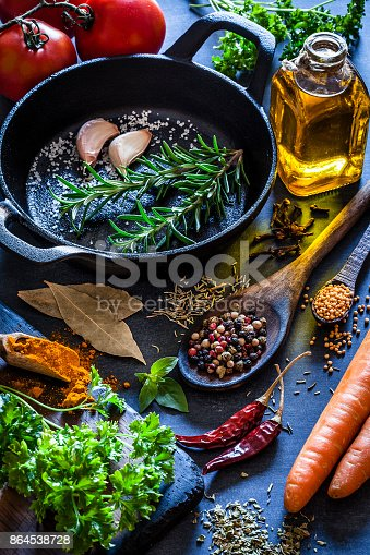 istock Cooking: black cast iron pan with spices and herbs on dark kitchen table 864538728