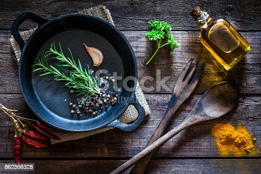 istock Cooking: black cast iron pan with spices and herbs on wooden kitchen table 862366328