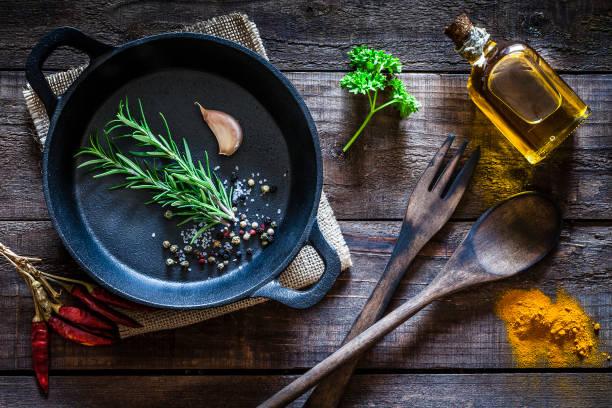kookfaciliteiten: zwarte gietijzeren pan met specerijen en kruiden op houten keukentafel - oil kitchen stockfoto's en -beelden