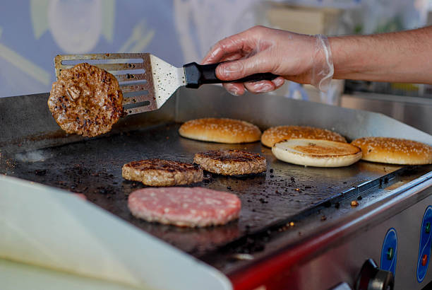 Cooking burgers in a fastfood stock photo