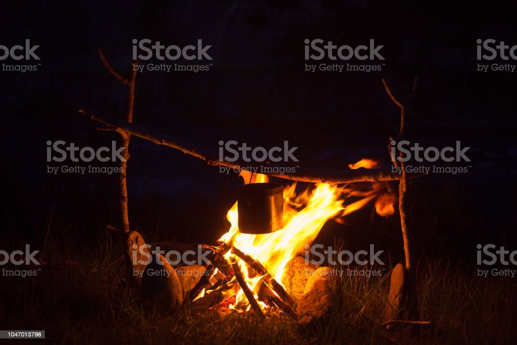 Cooking camp food in cauldron on open fire at night stock photo