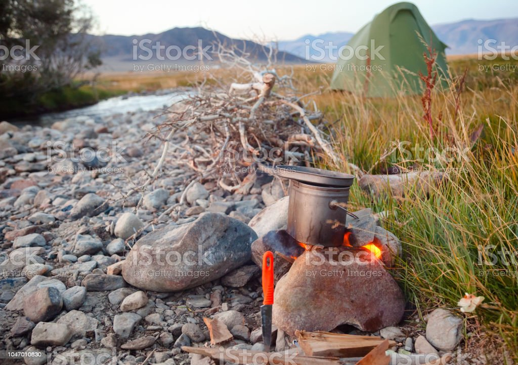 Cooking camp food in cauldron on open fire outdoors stock photo