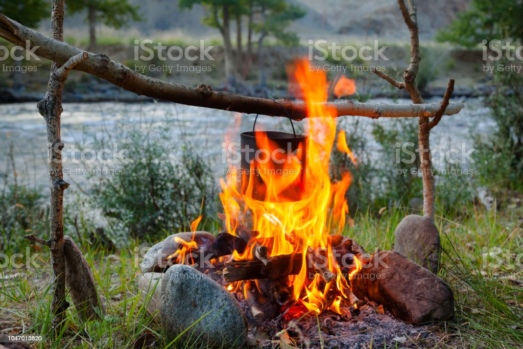 Cooking camp food in cauldron on open fire stock photo