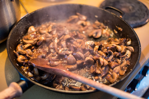 Cooking Champignons Mushroom With Wooden Flipper A Stir In Pan Stock Photo & More Pictures of Brown
