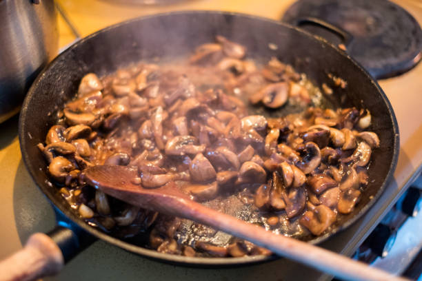 kochen champignons pilz mit hölzernen flipper aufsehen in pfanne - pilzpfanne stock-fotos und bilder