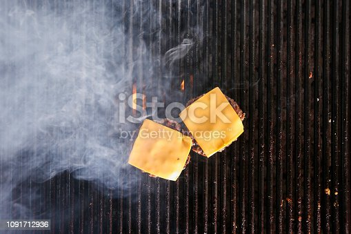 BBQ cooking cheeseburgers on a hot flaming grill