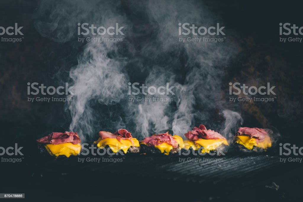 BBQ cooking cheeseburgers on a hot flaming grill stock photo