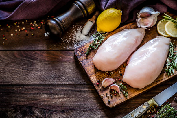 Cooking chicken breast Top view of two chicken breasts on a cutting board surrounded by various ingredients for seasoning like garlic, some aromatic herbs like thyme and rosemary, lime, salt and pepper, a kitchen knife and a pepper shaker on a rustic wooden table. Objects are at the right side and at the top of the image leaving a useful copy space for a text or a logo. Predominant color is dark brow. Low key DSLR photo taken with Canon EOS 6D Mark II and Canon EF 24-105 mm f/4L chicken breast stock pictures, royalty-free photos & images