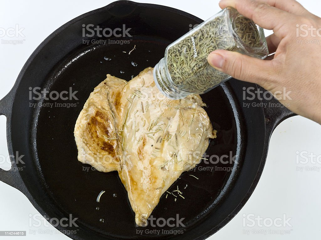 Cooking chicken Breast with dried rosemary royalty-free stock photo