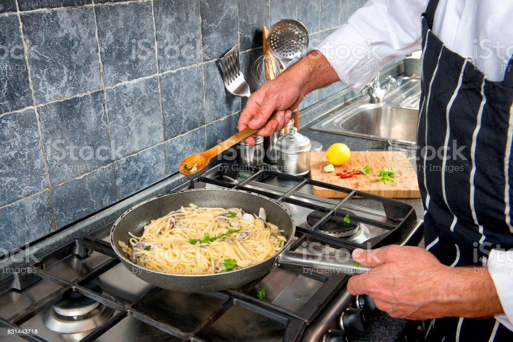 Cooking clams sauce for italian spaghetti stock photo