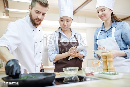 Low angle view at team of professional chefs working in modern restaurant kitchen standing round wooden table and cooking delicious dishes together, copy space