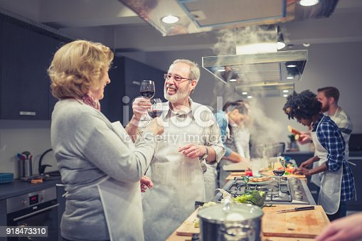 istock Cooking class participants enjoying cooking class, toasting with red wine 918473310