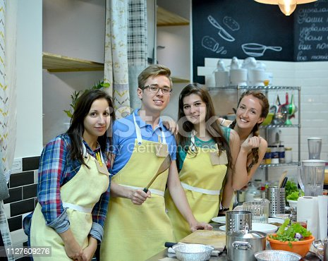 Group of three women and one man cooking and talking in the kitchen. Culinary, food and people, cooking class concept/Cooking class. young happy friends in the kitchen
