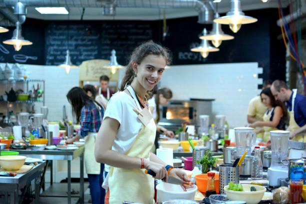cooking class. young happy friends in the kitchen - compagni scuola foto e immagini stock