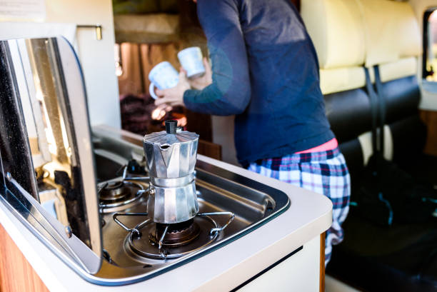 Cooking coffee in campervan, caravan or RV on camping trip. Cooking coffee in campervan, caravan or RV on camping trip. Woman is making coffee in the morning using italian kafetiera on a family vacation camping trip. rv interior stock pictures, royalty-free photos & images