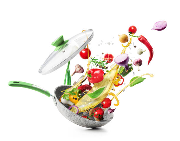 Cooking concept. Vegetables are flying out of the pan isolated on white background. Healthy food. stock photo