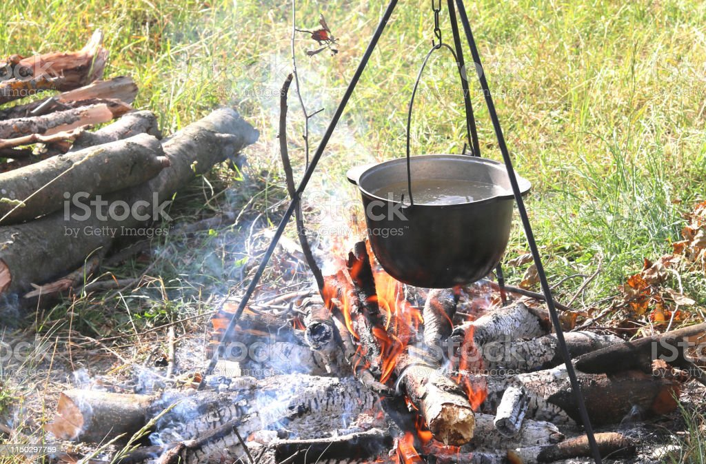 cooking delicious tasty food outdoors on fire in iron pot in summer...
