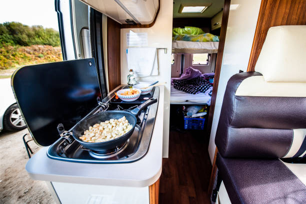 Cooking dinner or lunch in campervan, motorhome or RV. Cooking dinner or lunch in campervan, motorhome or RV. Preparing chicken  in a pan in camper van when traveling with RV, motor home caravan or motorvan. Vanlife or van life lifestyle on the road. caravan photos stock pictures, royalty-free photos & images