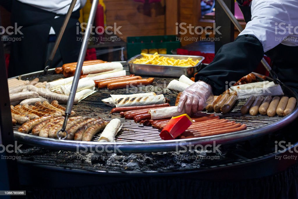 Cooking fast food on a huge grill at the fair. sausages and potatoes are grilled stock photo