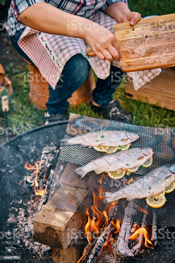Cooking Fish With Lemon Over Open Campfire Royalty Free Stock Photo