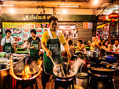 Bangkok, Thailand - February 26, 2016: A cook is preparing food in a restaurants with chairs and tables on the street at Chinatown Bangkok. This area is very popular because the diverse food stands that appear at night time.