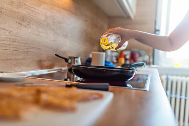 kokend voedsel, dat de olijf oi giet. - oil kitchen stockfoto's en -beelden