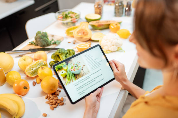 Cooking food using recipe on a digital tablet stock photo