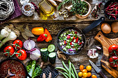 Top view of a rustic wooden table filled with fresh organic vegetables ready for cooking. The composition includes garlic, bell pepper,  tomatoes,  cucumber, broccoli, onion, lettuce, and chili peppers. An iron pan with chopped vegetables is at the center of the frame. An olive oil bottle and a mortar are at the top of the frame. DSRL studio photo taken with Canon EOS 5D Mk II and Canon EF 100mm f/2.8L Macro IS USM