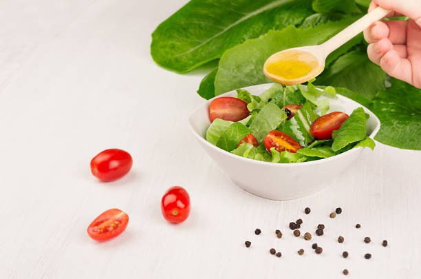 cooking fresh spring salad of grees, cherry tomato slices on white wood background, copy space. hand holds spoon and olive oil flow down on salad. - perdita di peso foto e immagini stock