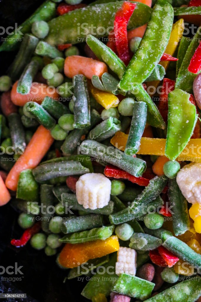 cooking frozen vegetables in  hot skillet. Defrosting and roasting the vegetable mix stock photo
