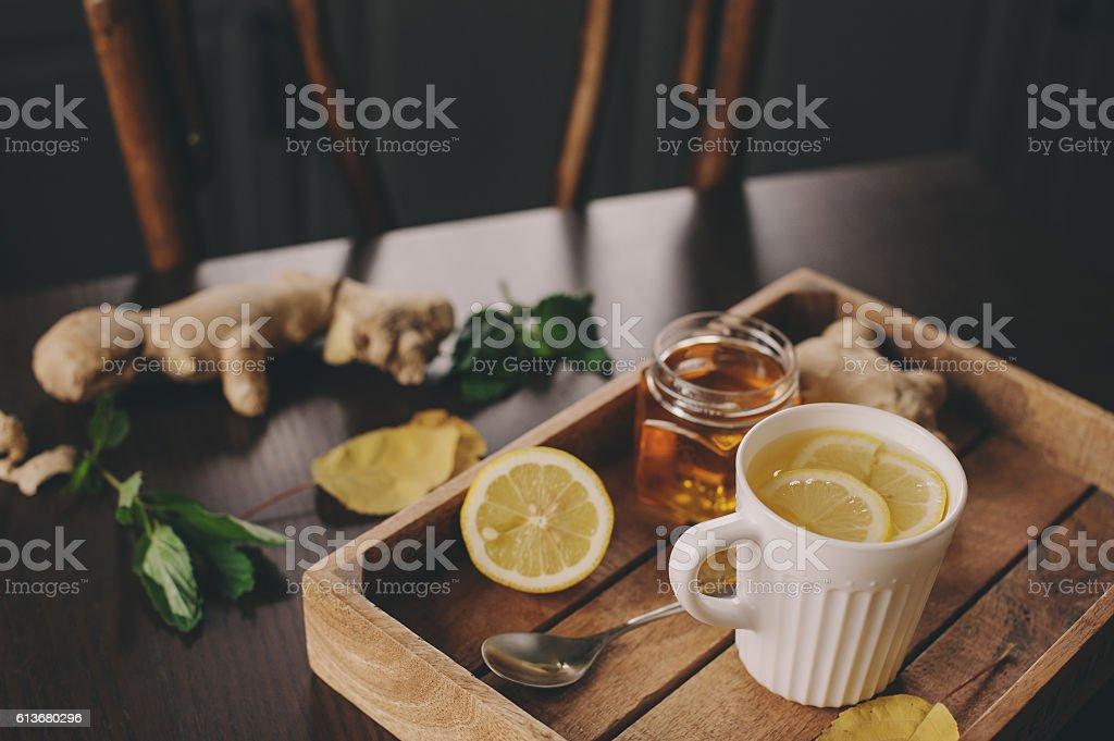 cooking ginger, lemon and honey tea in dark rustic interior stock photo