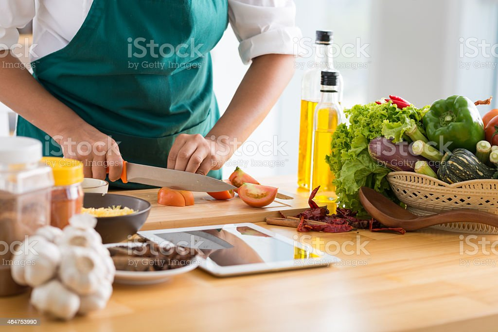 Cooking healthy meal Woman following recipe on digital tablet and cooking healthy meal 2015 Stock Photo