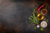 Cooking background, herbs, salt, spices, olive oil, dark rusty background copy space top view