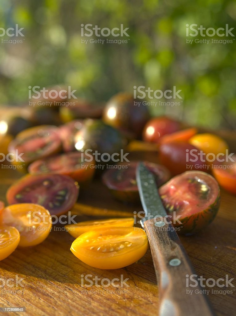 Cooking Homegrown Produce, Heirloom Tomatoes Sliced for Summer Dinner Salad royalty-free stock photo