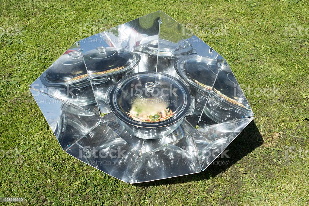 Cooking in a solar oven on the grass. stock photo