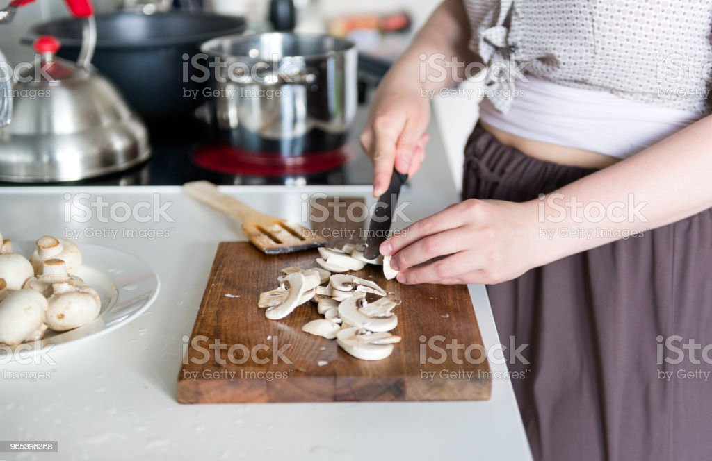 cooking in the home kitchen, the girl cuts mushrooms with a knife on the cutting Board zbiór zdjęć royalty-free