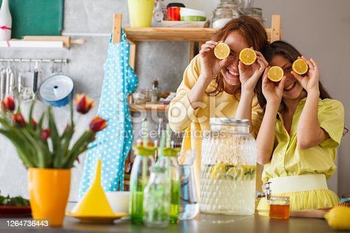 Front view of happy female family members playing with lemons as eyes after making tasty refreshing lemon juice in a colorful kitchen.