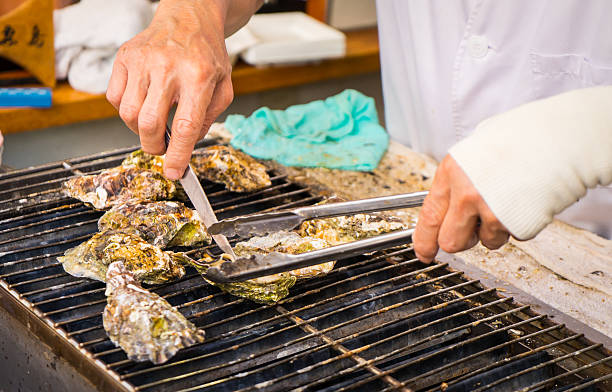 Cooking Japanese Fresh Oysters Cooking Japanese Fresh Oysters miyajima stock pictures, royalty-free photos & images