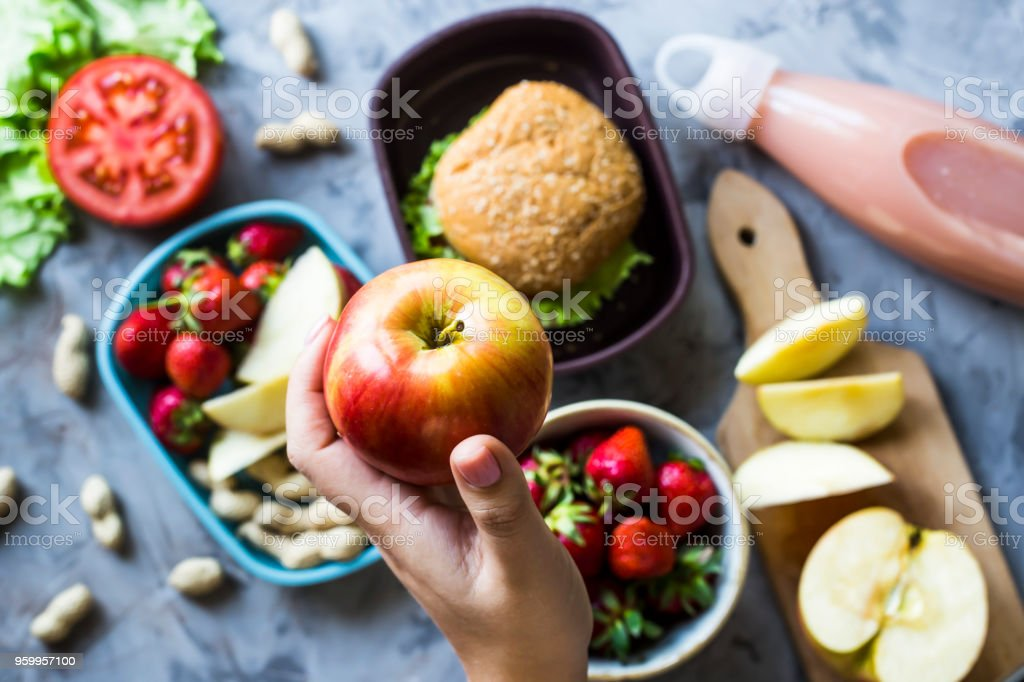 Cooking lunch for the child to school. On the gray kitchen table. Sandwich, strawberries and peanuts in lunchboxes. Top view. Woman holding an apple royalty-free stock photo