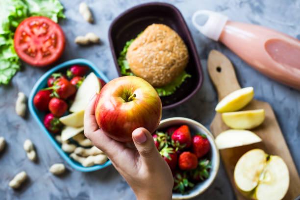 학교에 아이 위한 요리 점심입니다. 회색 부엌 테이블에. 샌드위치, 딸기와 도시락에 땅콩입니다. 최고의 볼 수 있습니다. 여 자가 사과 들고 - 점심 뉴스 사진 이미지