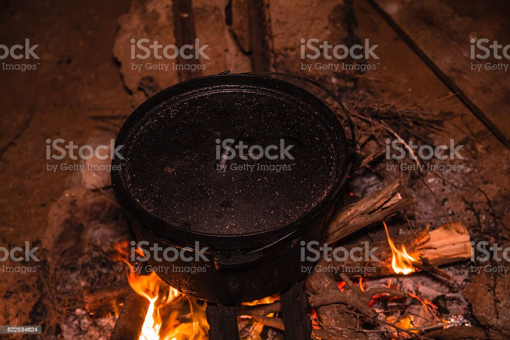 Cooking meal in cauldron on burning campfire at night stock photo
