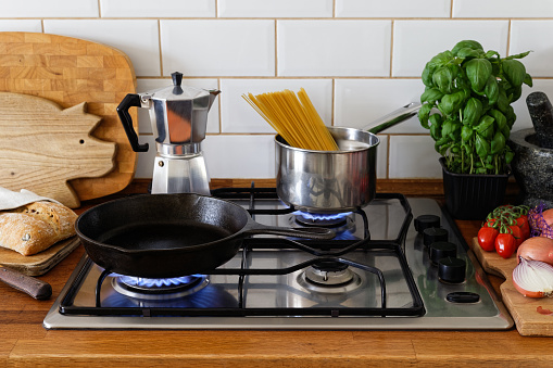Cooking meal on a gas stove in traditional home kitchen. Wood worktop.